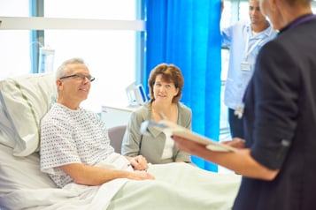 Male patient in hospital bed talking to a nurse